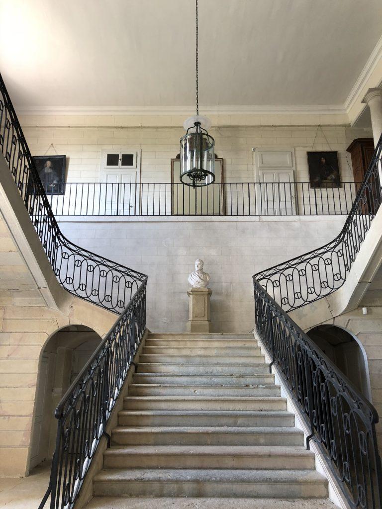 Un buste en pierre encadré d'escaliers d'époque