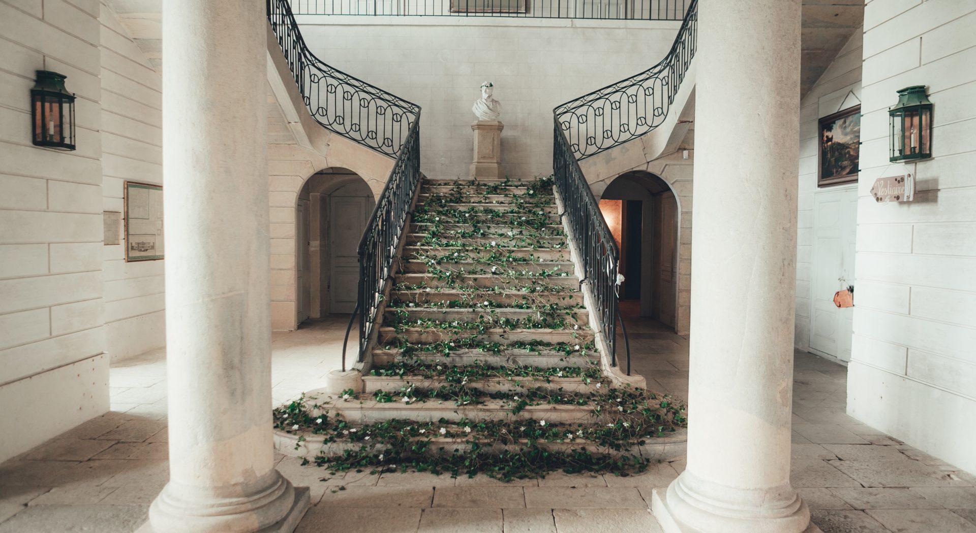 Un escalier et ses piliers d'époque, recouverts de lierre