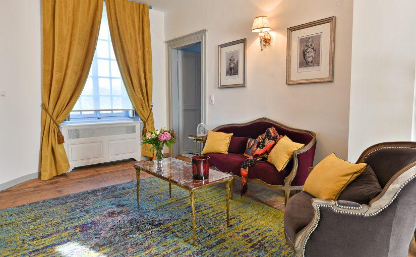 Le coin canapé avec une fenêtre lumineuse et ses rideaux